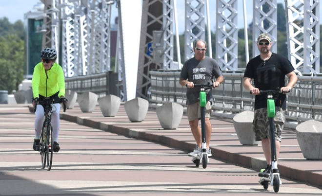 People ride Lime electric scooters on the John Seigenthaler Pedestrian Bridge on Aug. 31, 2018.